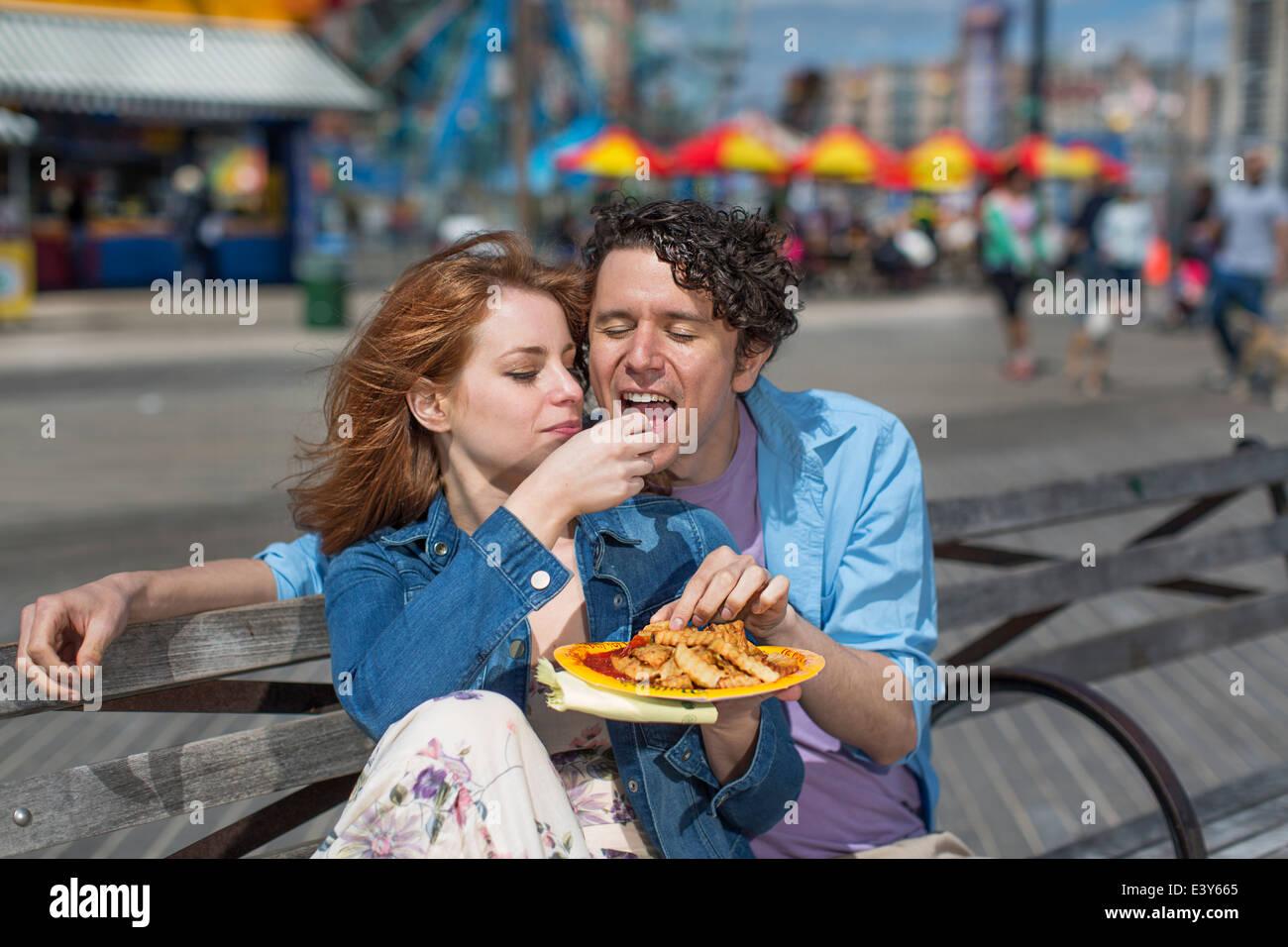 Romantisch zu zweit essen Chips im Freizeitpark Stockbild