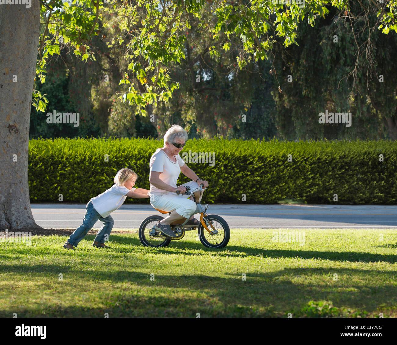Drei Jahre alter Junge drängen Großmutter auf Zyklus im park Stockbild
