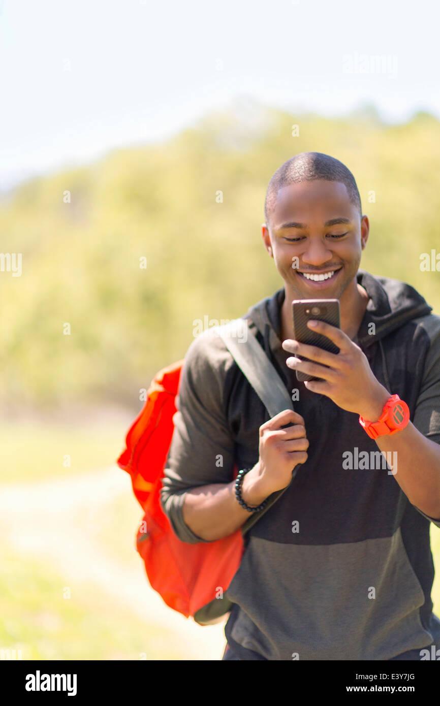 Junge männliche Wanderer lesen Nachricht auf smartphone Stockbild