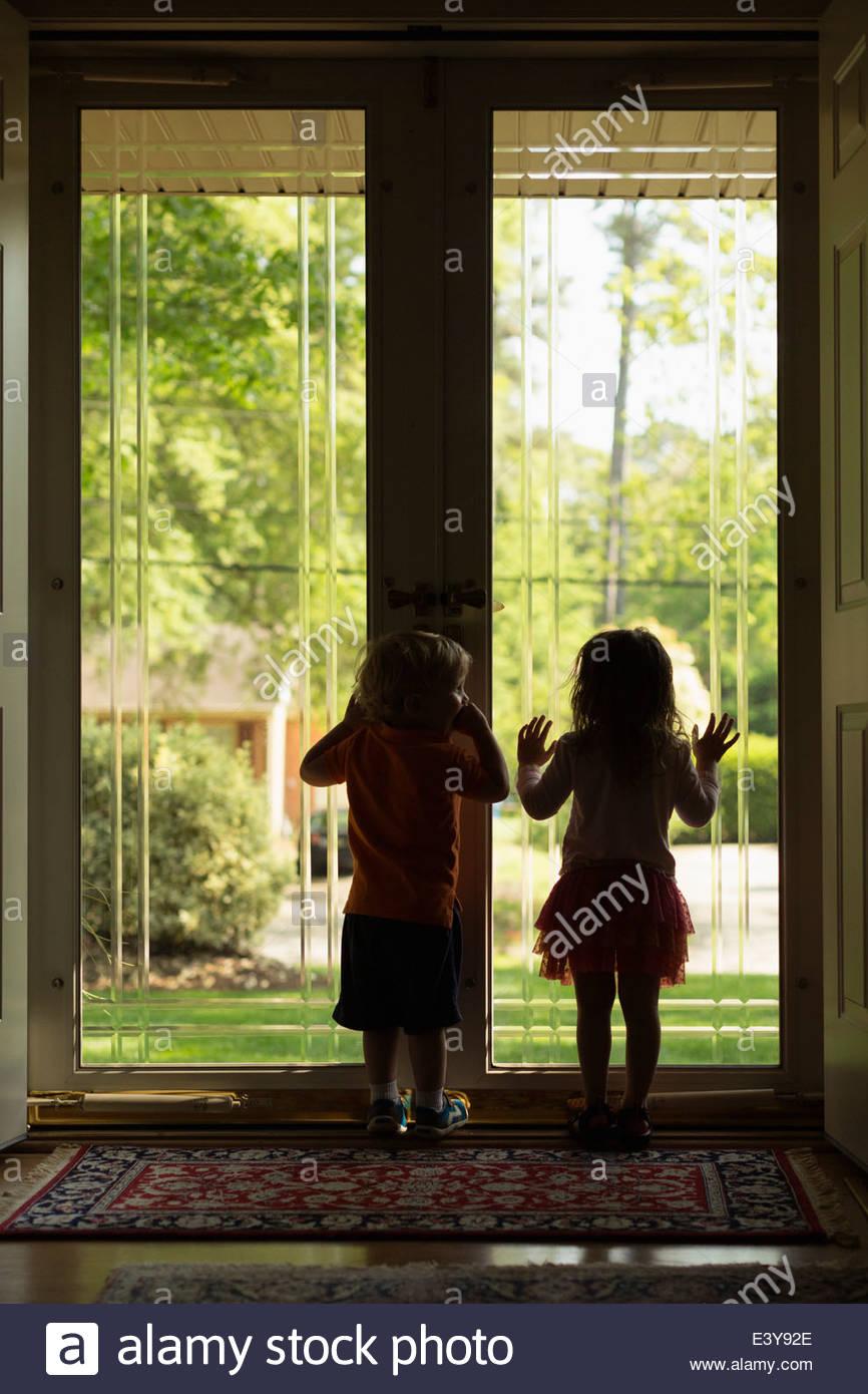 Männlichen und weiblichen Kleinkind Freunde Silhouette durch die Terrassentür Stockbild