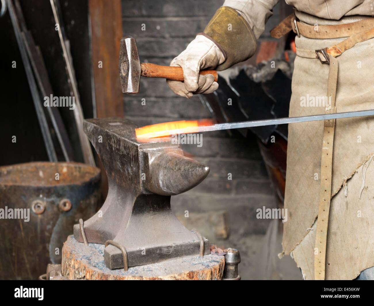 Bild der Schmiede Hämmern eine rote Roheisen Rute abgeschnitten Stockbild