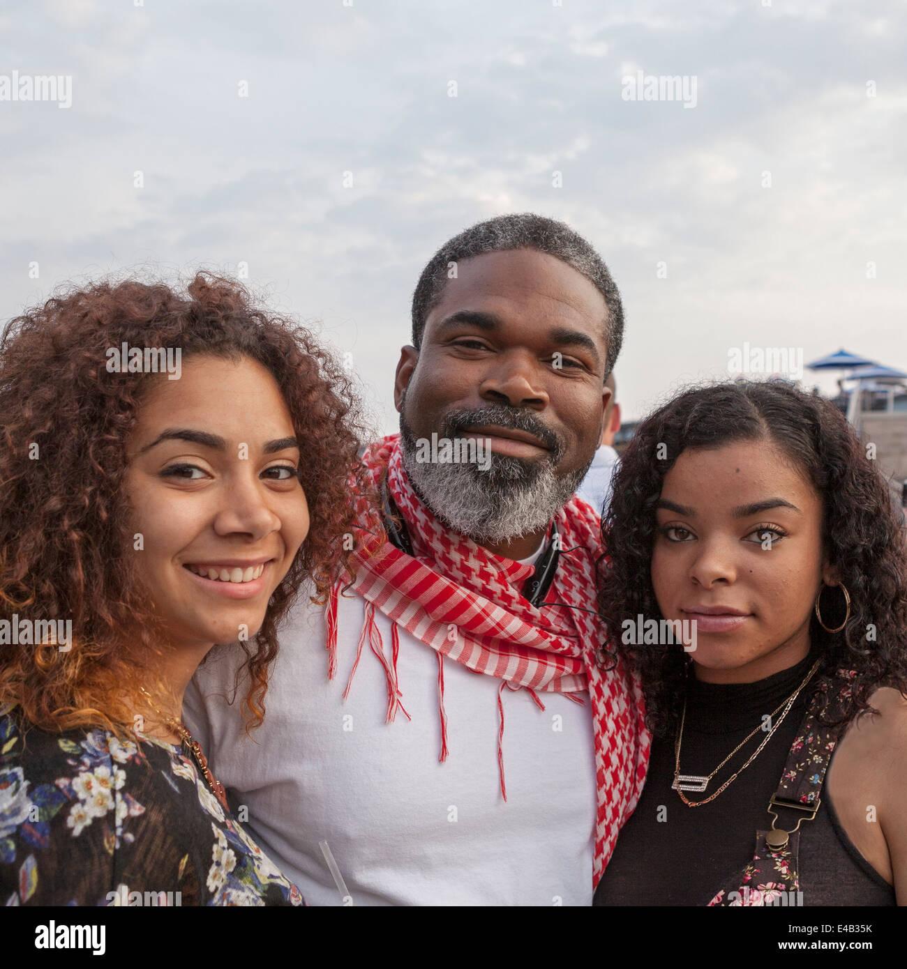 Ein Vater steht mit seinen beiden Töchtern beim Sommerfest, ein jährliches Musikfestival in Milwaukee, Stockbild