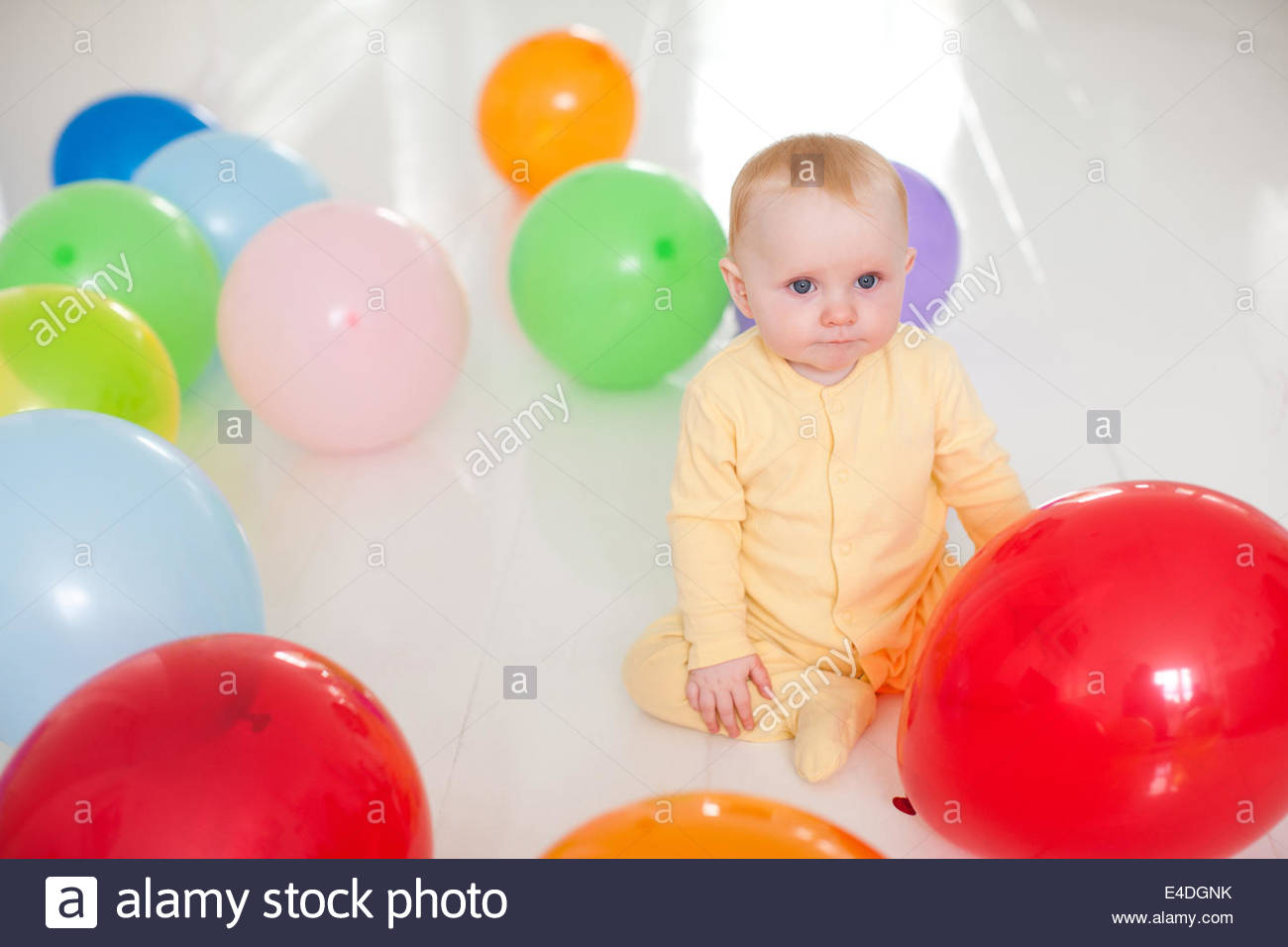 Neugierig Baby mit Luftballons Stockbild