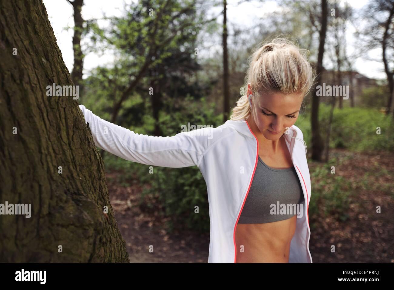 Schöne junge Frau, die nach dem Joggen in einem Park von einem Baum ausruhen. Passen Sie weiblichen Athleten Stockbild