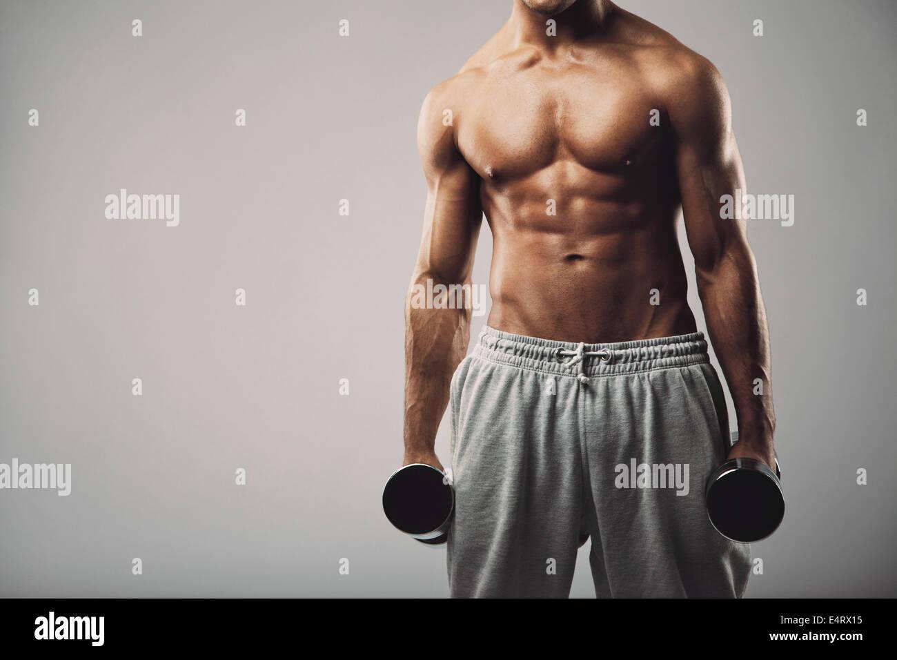 Studio Aufnahme eines männlichen Modells in Jogginghose mit Hanteln in beiden Händen auf grauem Hintergrund Stockbild