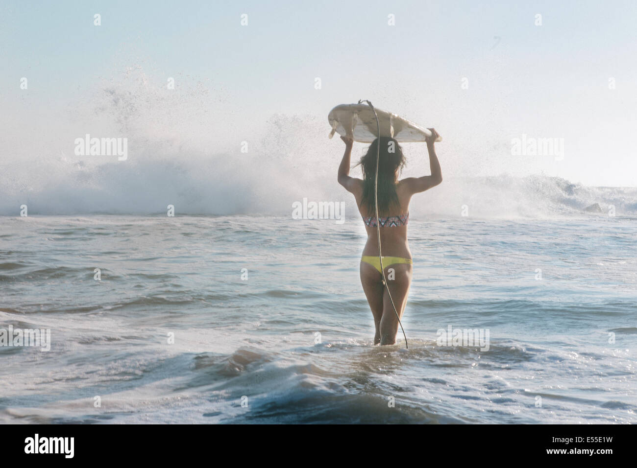 Junge weibliche Surfer mit Surfbrett auf Kopf zu Fuß in Richtung brechenden Wellen Stockbild