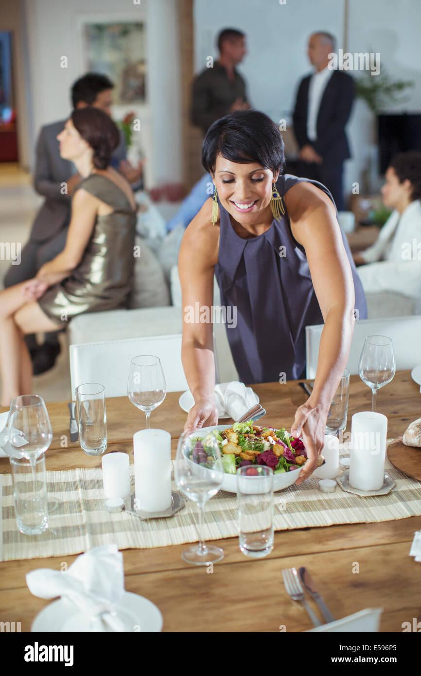 Frau serviert Essen zu Dinner-party Stockbild