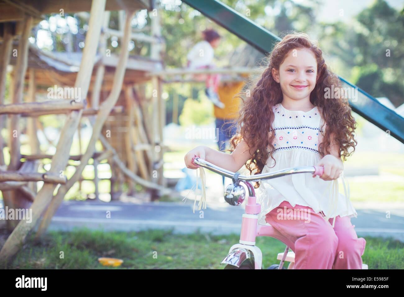 Lächelndes Mädchen sitzen auf dem Fahrrad am Spielplatz Stockbild