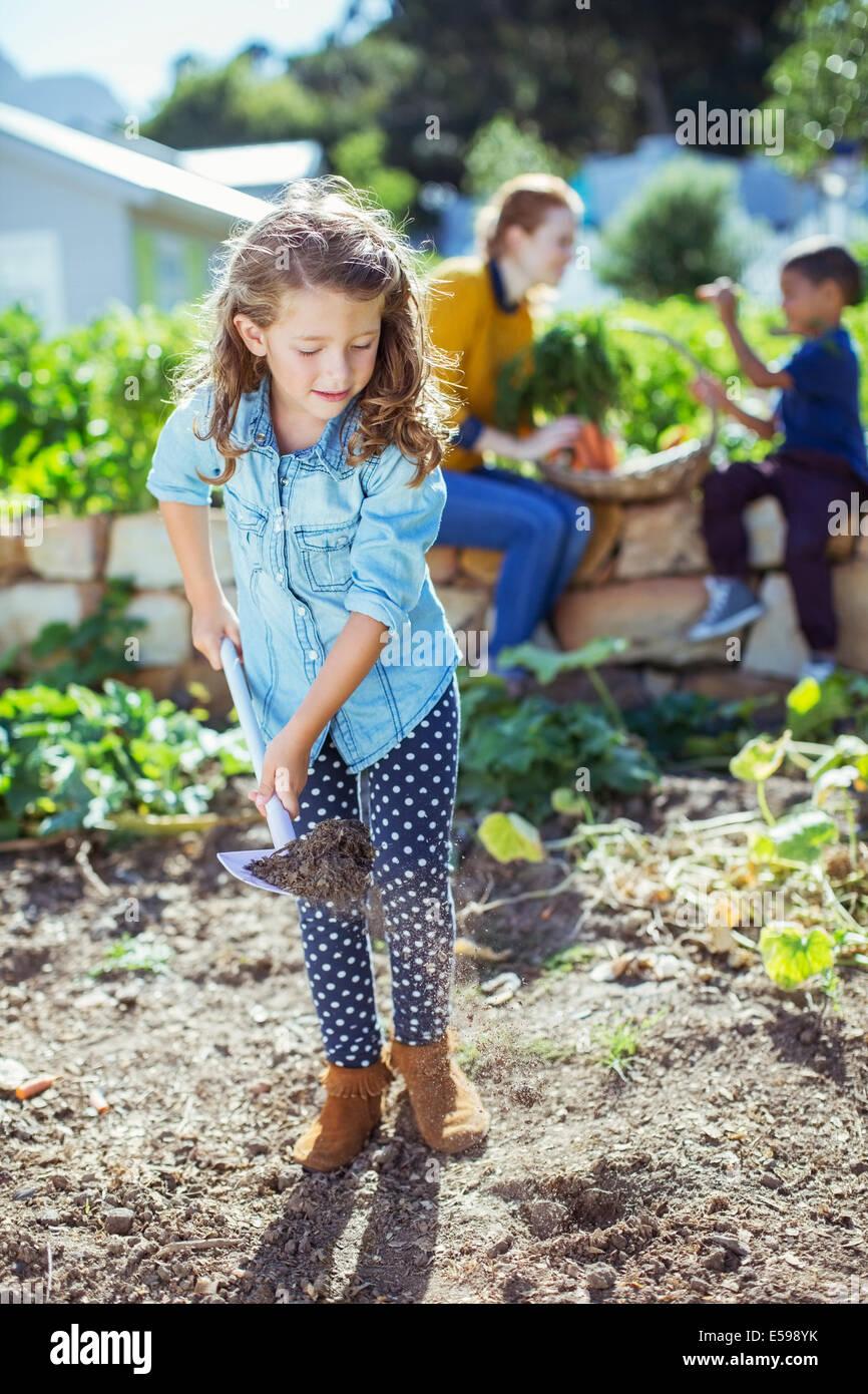 Mädchen, die Schaufeln Schmutz im Garten Stockbild