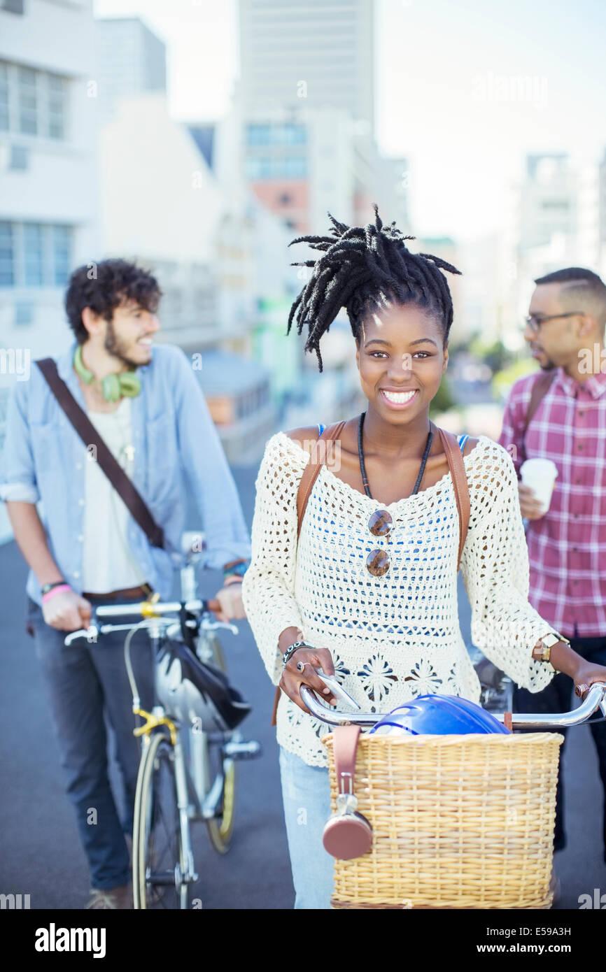 Freunde drängen Fahrräder auf Stadt Straße Stockbild