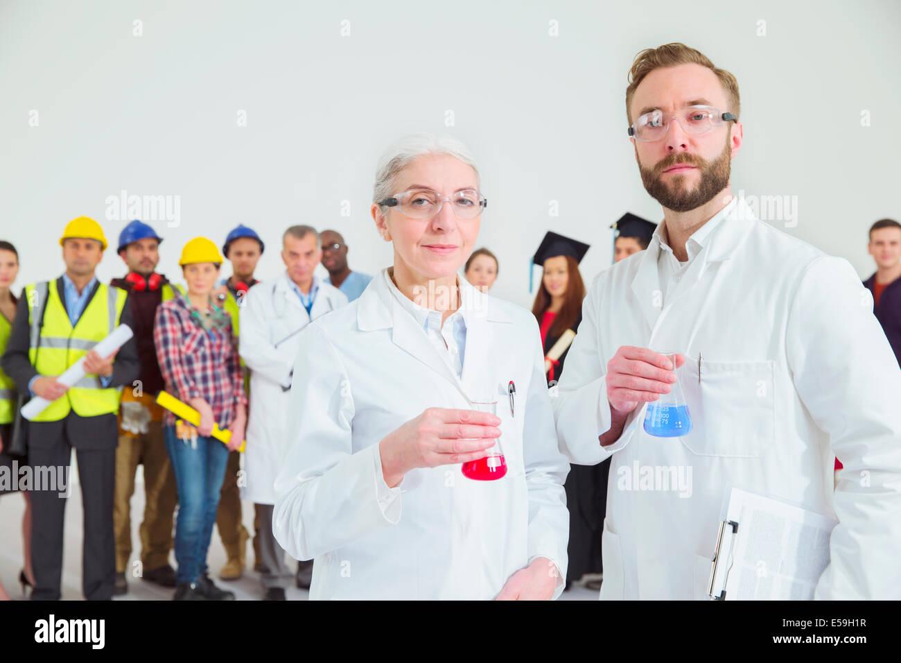 Porträt von Wissenschaftlern mit Mitarbeitern im Hintergrund Stockbild