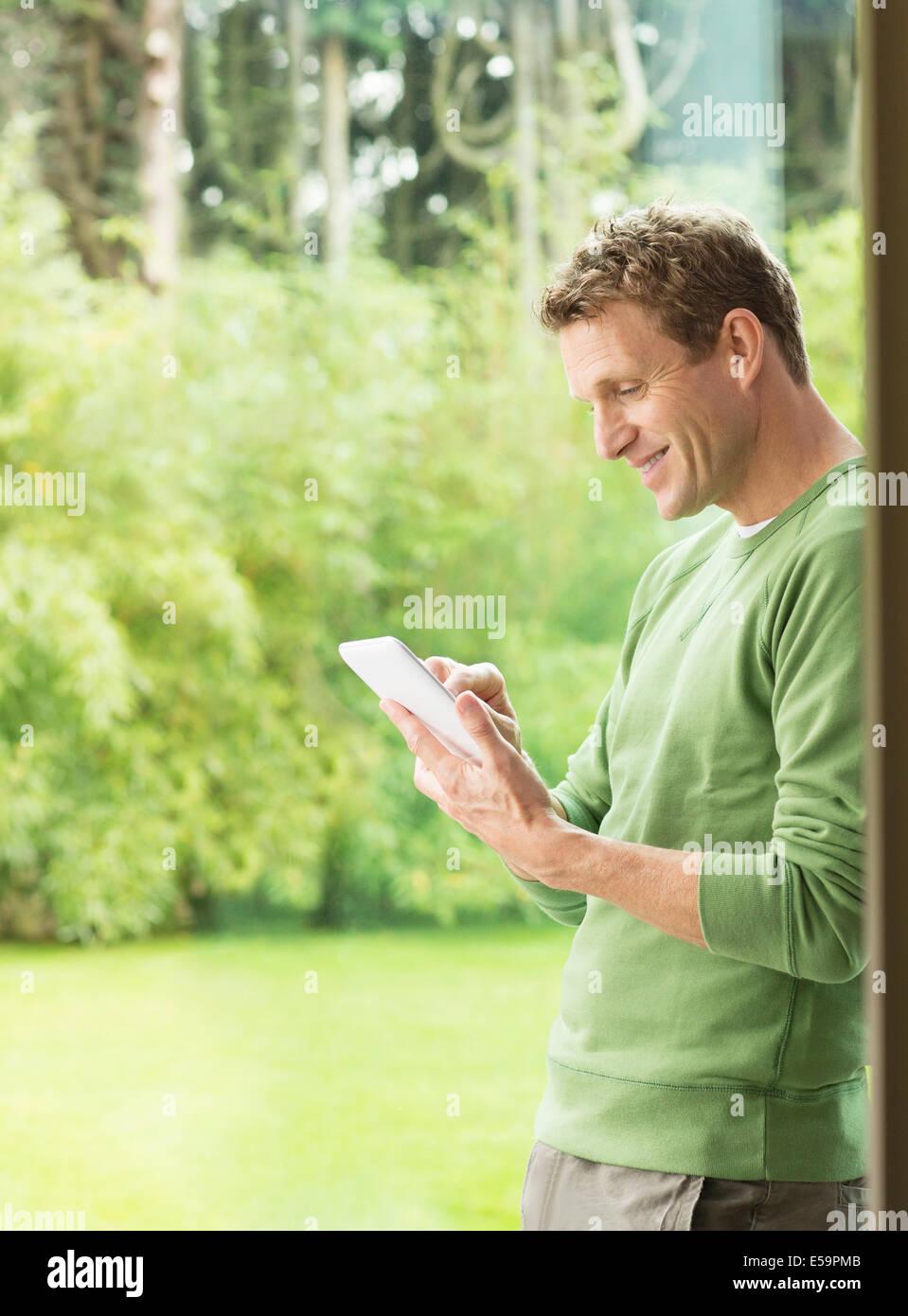 Mann mit digital-Tablette durch Fenster Stockbild
