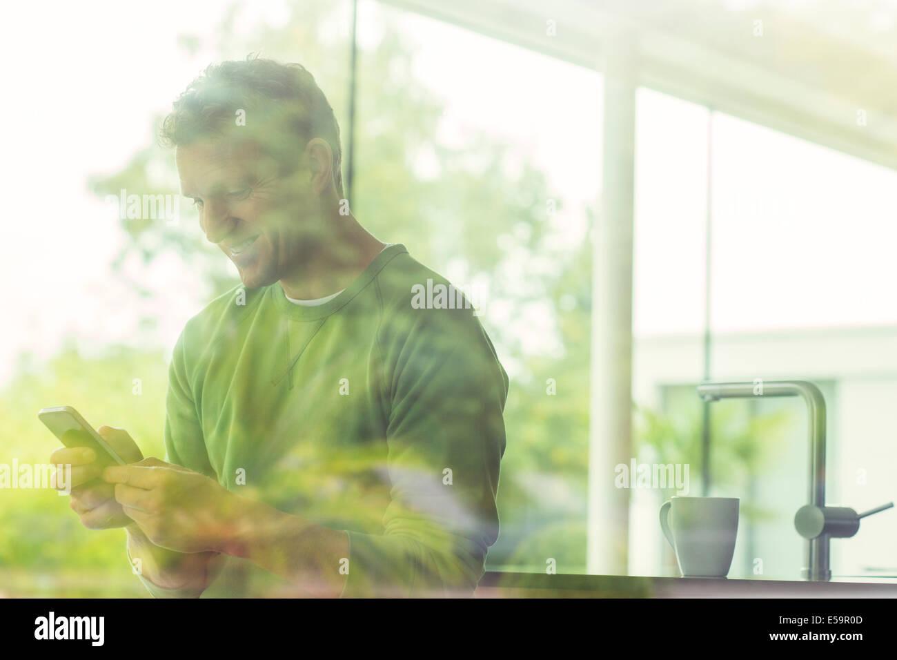 Mann mit Handy über Fenster angezeigt Stockbild