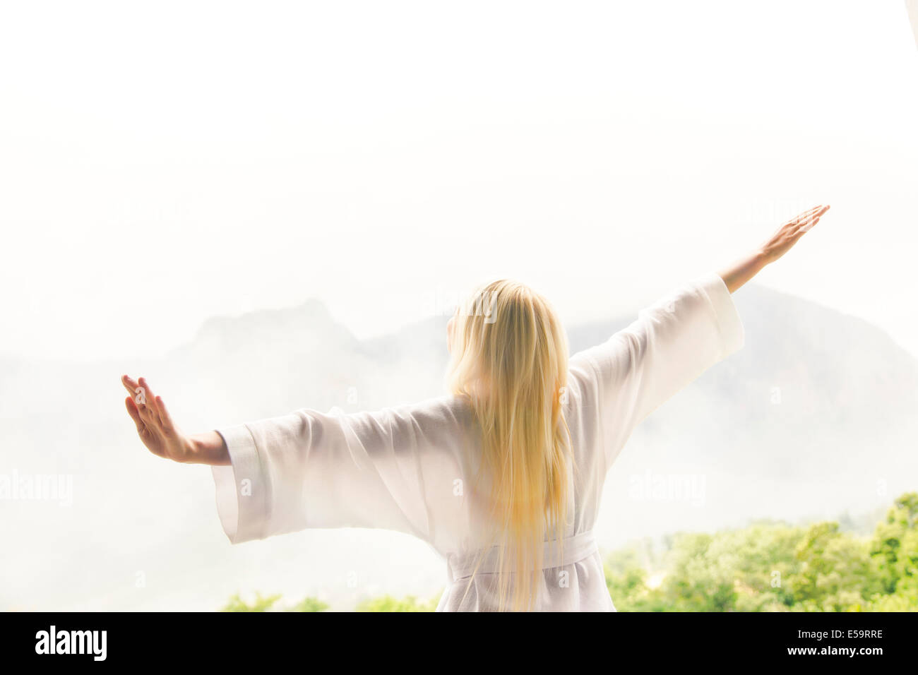 Frau im Bademantel mit Blick auf Landschaft Stockbild