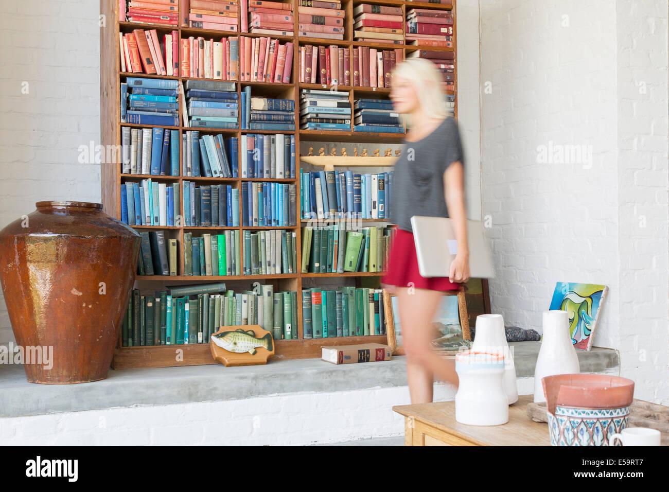 Verschwommene Sicht auf Frau zu Fuß von Bücherregalen Stockbild