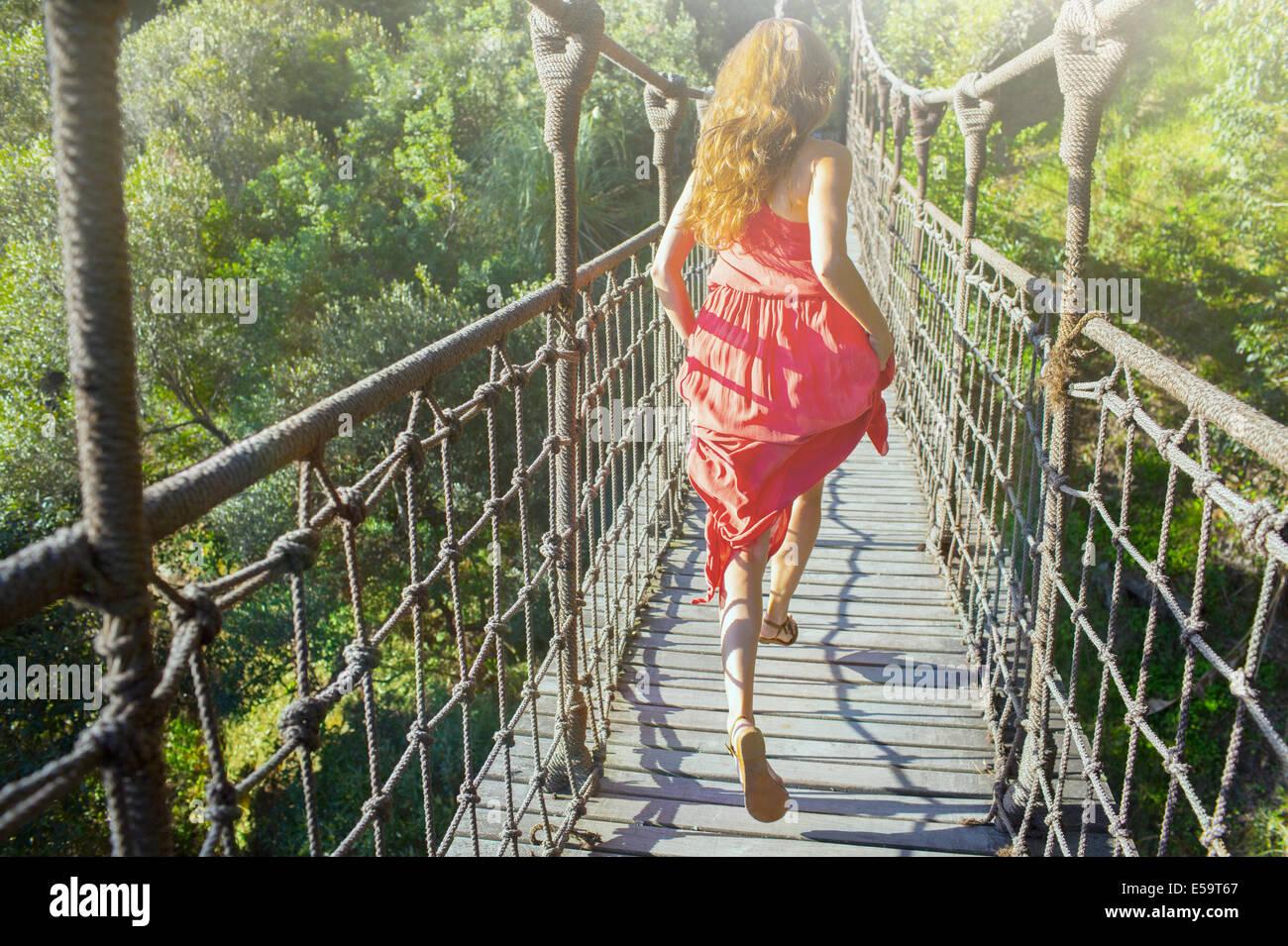 Frau zu Fuß auf hölzerne Hängebrücke Stockbild