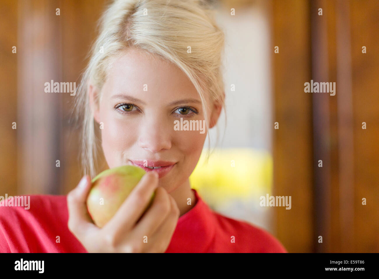 Frau zu essen Apfel im Innenbereich Stockbild