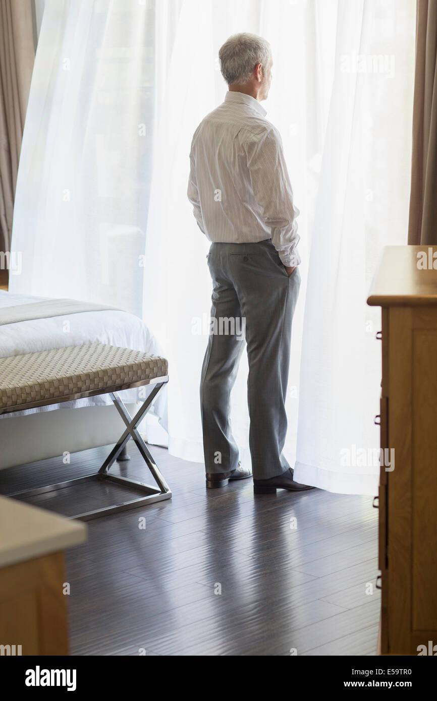 Geschäftsmann aus Fenster im Hotelzimmer Stockbild