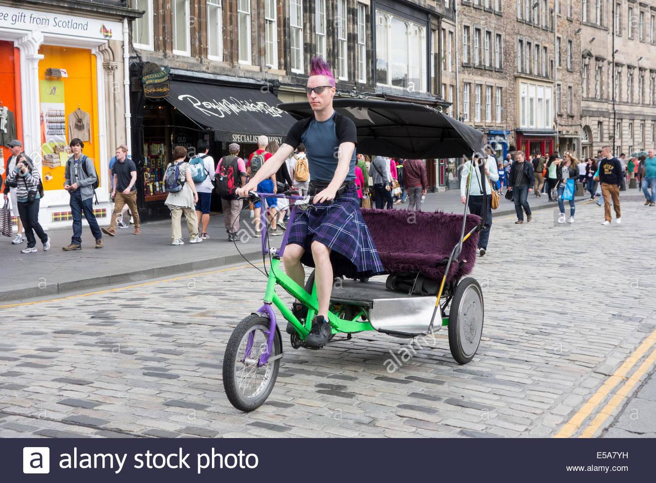 Rikscha-Betreiber einen Tartan Kilt tragen, beim Radfahren auf der Royal Mile in Edinburgh, Schottland. Stockbild