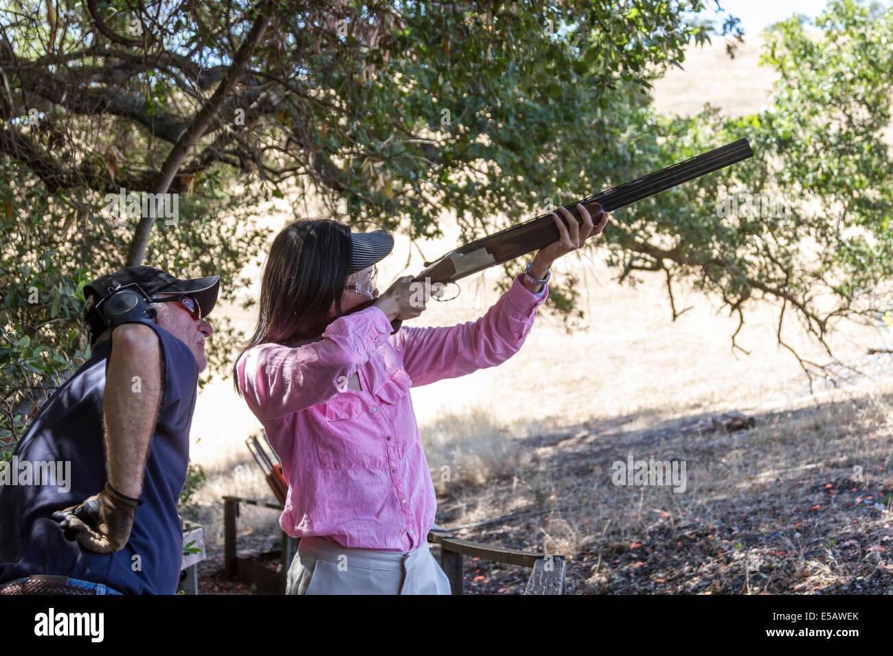 Asiatische Frau Tone mit einer Schrotflinte schießen, wie ihr Lehrer lehrt wie man schießt Stockbild