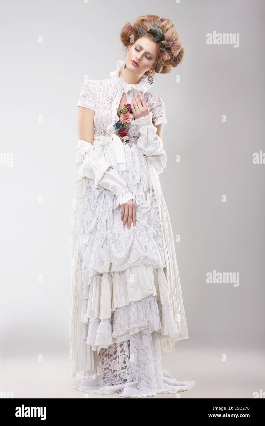 Wunderschöne Outre weiblich in Spitzen weißen Kleid mit Blumen Stockbild