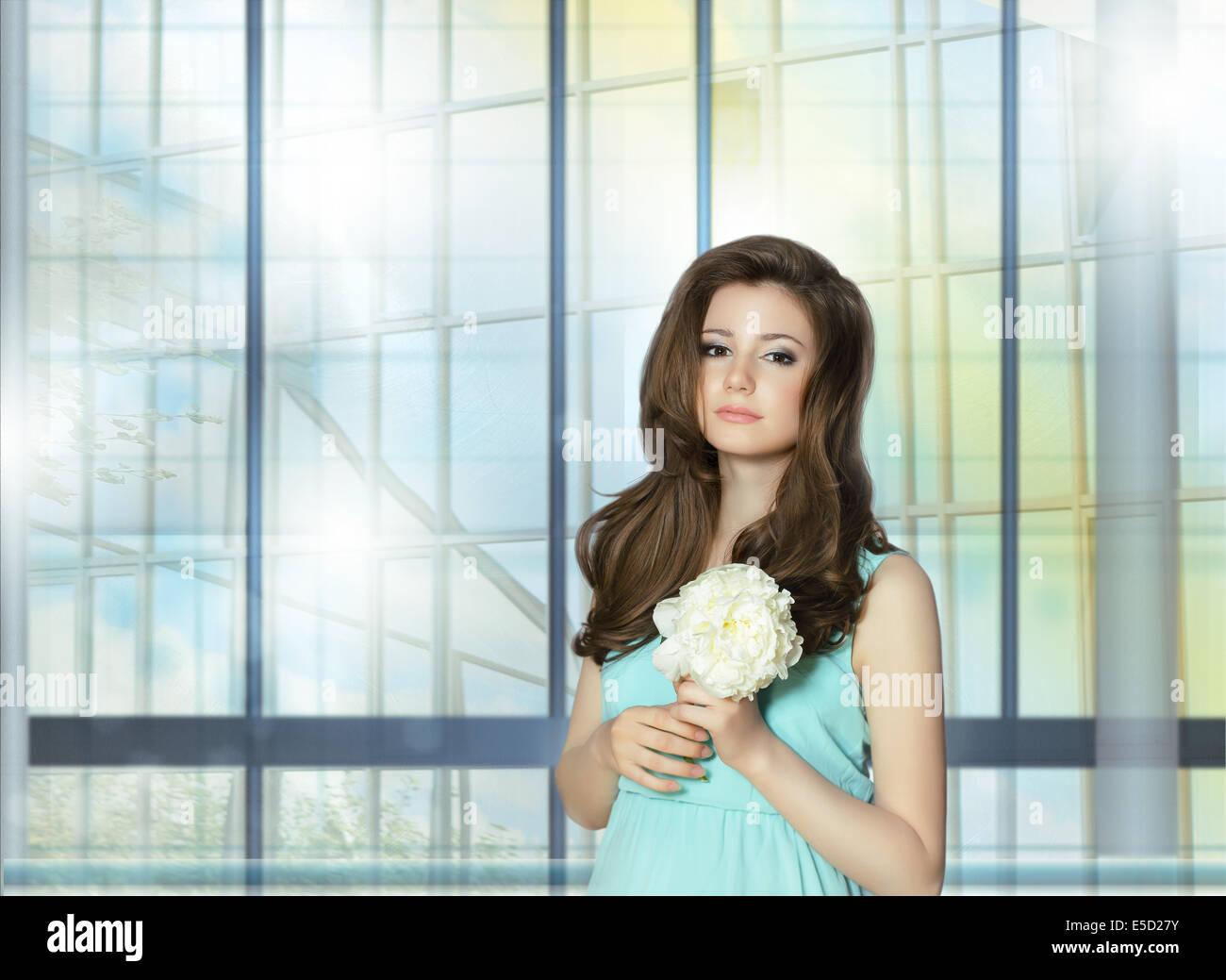 Junge Frau, die Pfingstrose Blume über das Fenster Stockbild