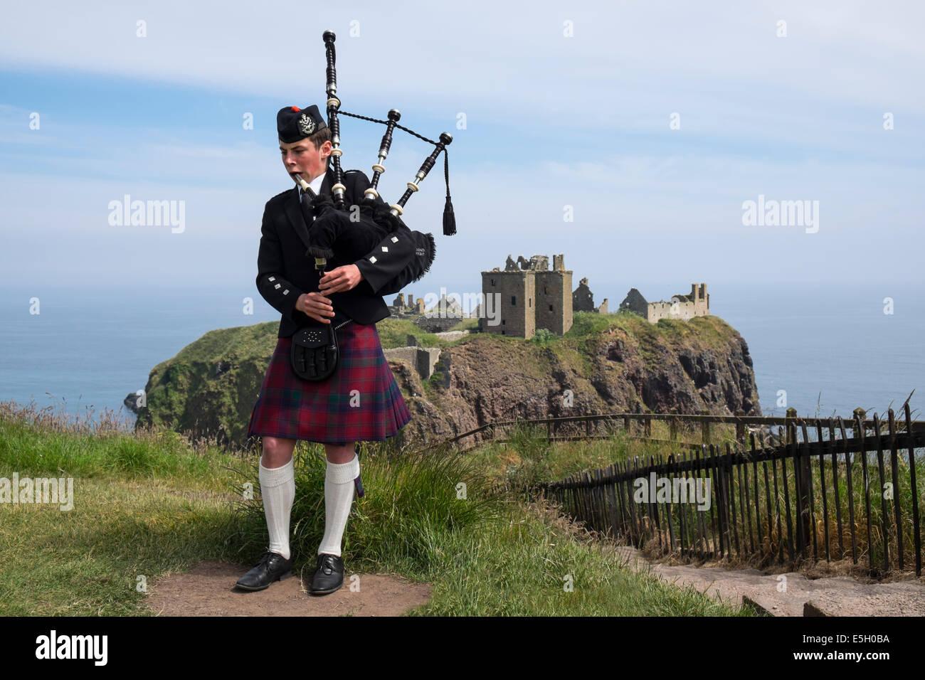 Piper spielen Rohre in traditionellen schottischen Kilt Dunnottar Castle in Aberdeenshire Scotland UK Stockbild