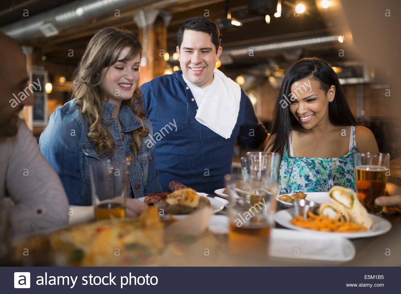 Kellner servieren von Speisen mit Freunden im pub Stockbild