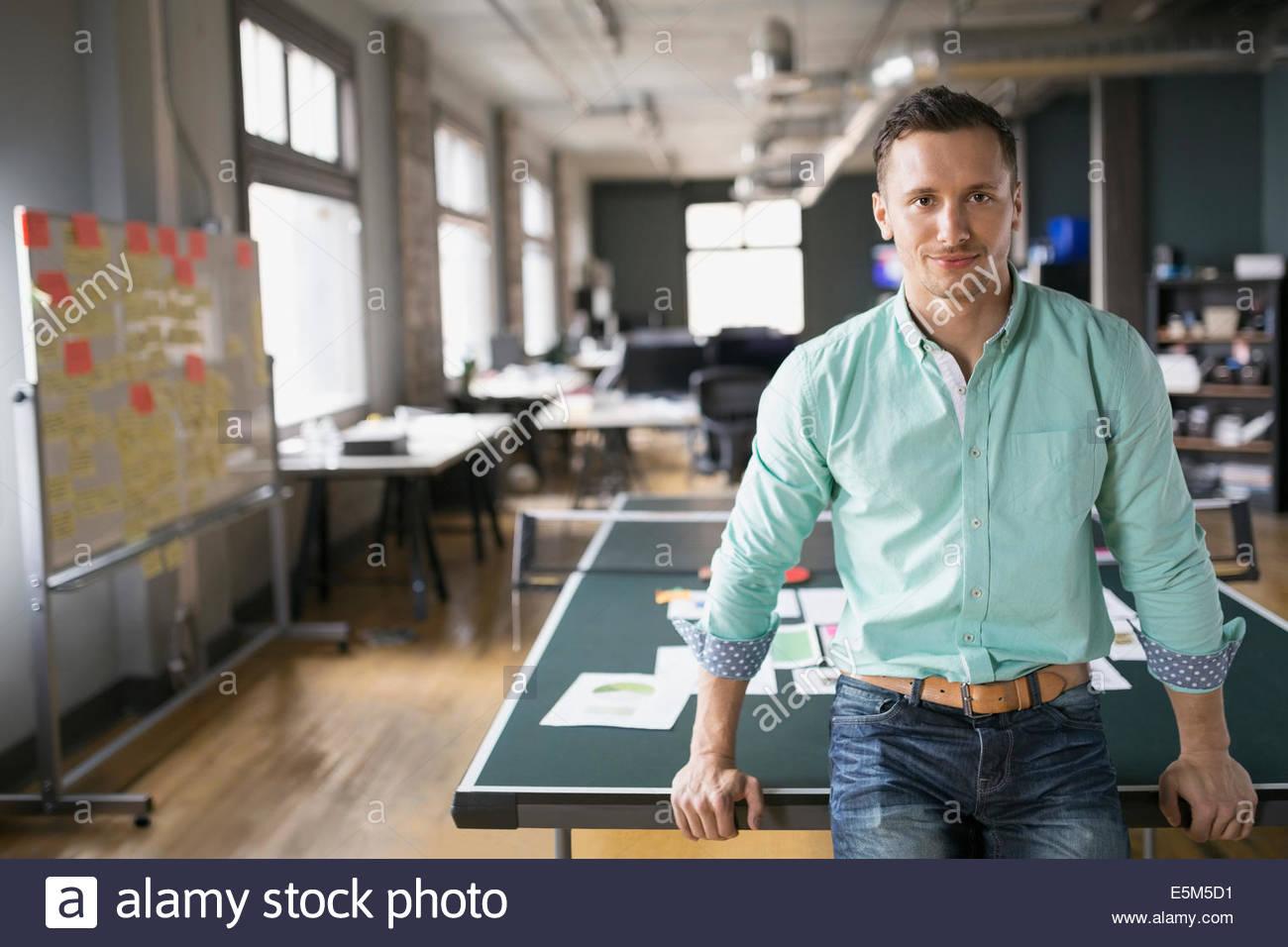 Kreative Geschäftsmann stützte sich auf Ping-Pong-Tisch Stockbild