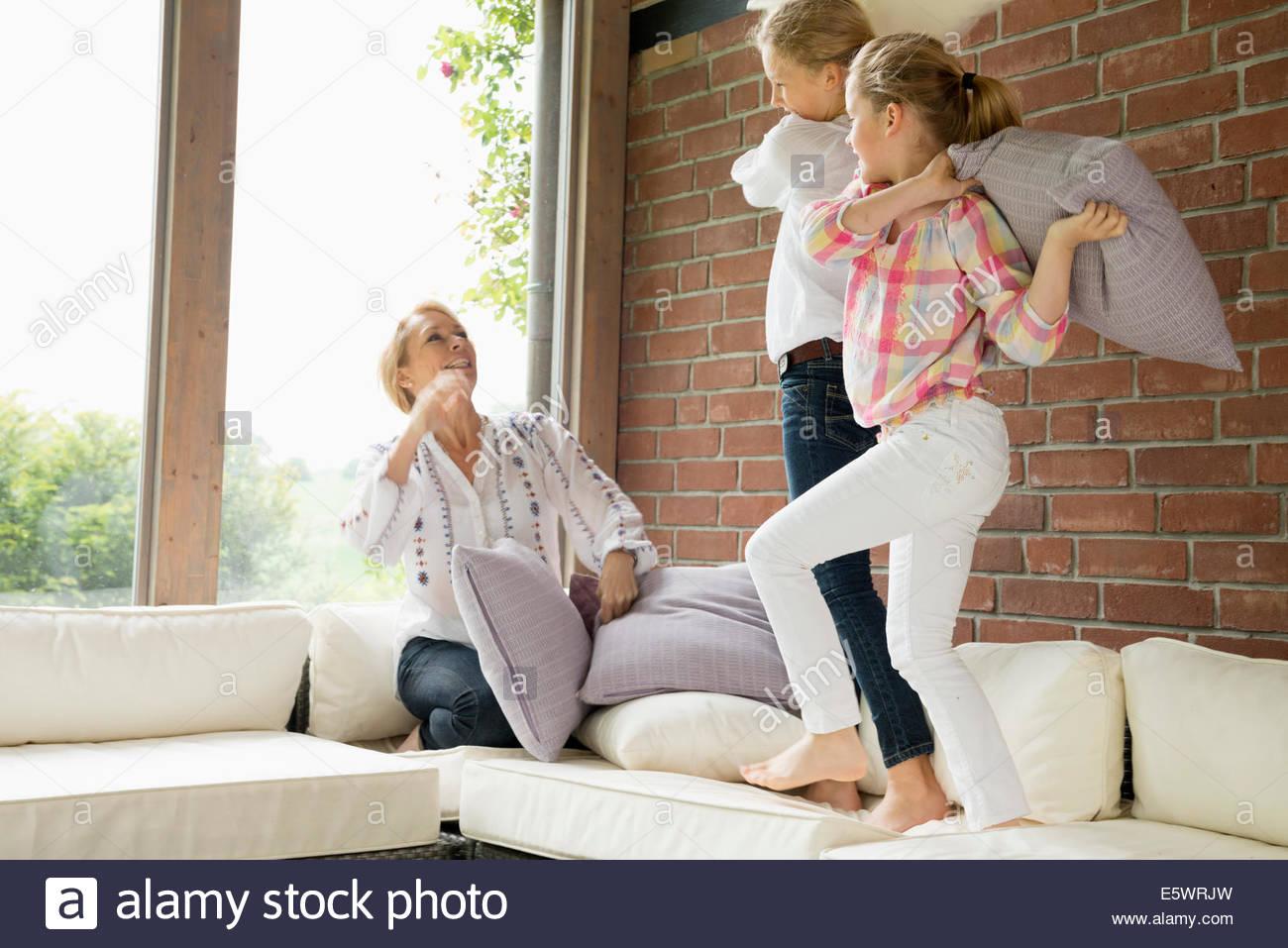 Mutter mit Töchtern mit Kissenschlacht Stockbild