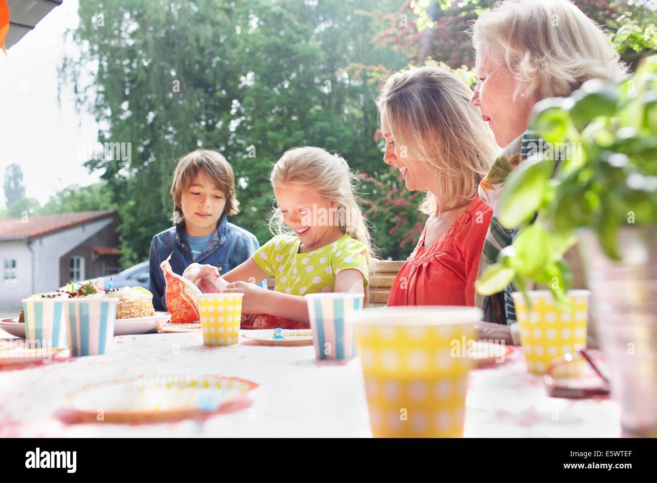 Mädchen mit ihrer Familie auf Geburtstagsparty Geburtstagsgeschenk öffnen Stockbild