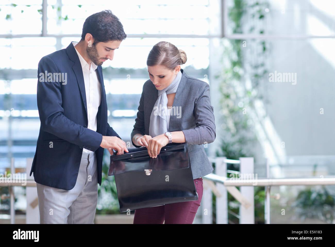 Geschäftsmann und Geschäftsfrau Eröffnung Aktentasche im Konferenz-Center atrium Stockbild