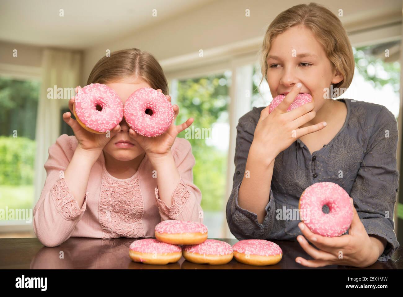 Zwei Schwestern ein Donut Löcher über den Augen, die anderen Essen Stockbild