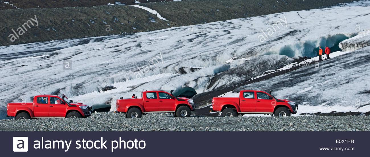 Panoramablick von Wanderern, die Höhle und eine Reihe von Geländewagen, Breidamerkurjokull, East Island, Stockbild