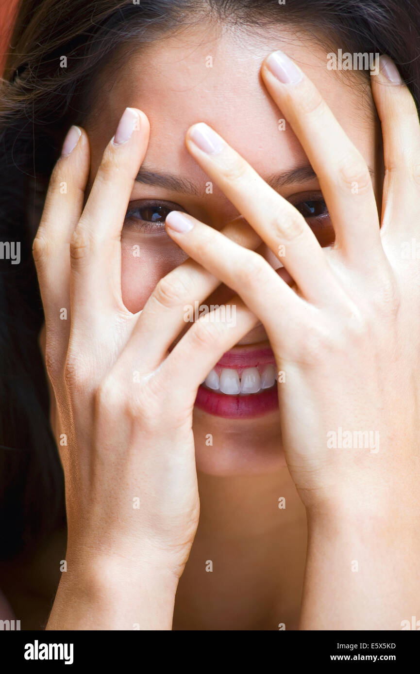 Porträt der jungen Frau mit Händen bedeckte Gesicht Stockbild