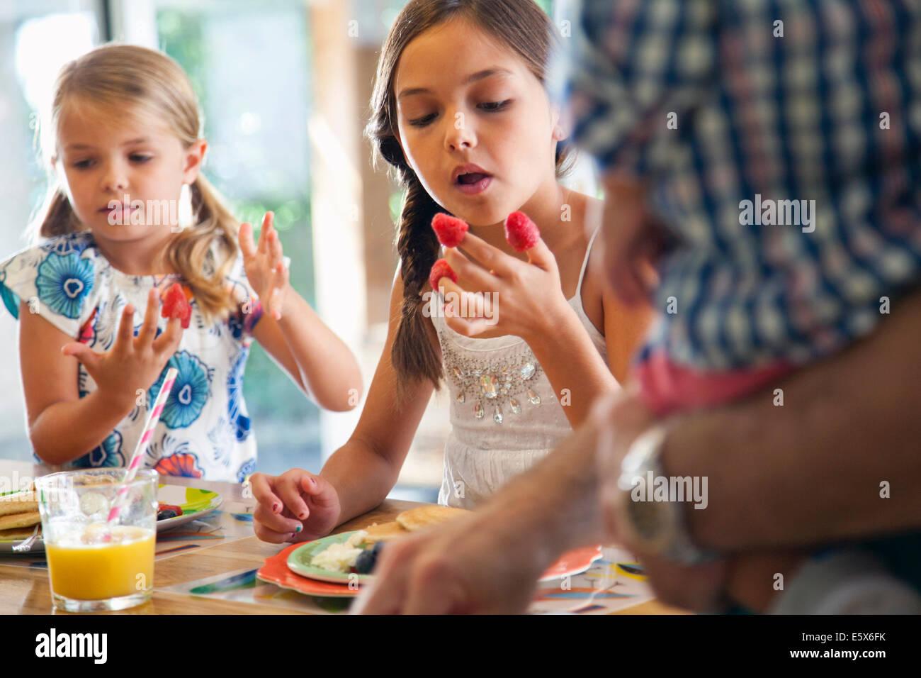 Zwei Schwestern mit Himbeeren an ihren Fingern an Küche Frühstücksbar Stockbild