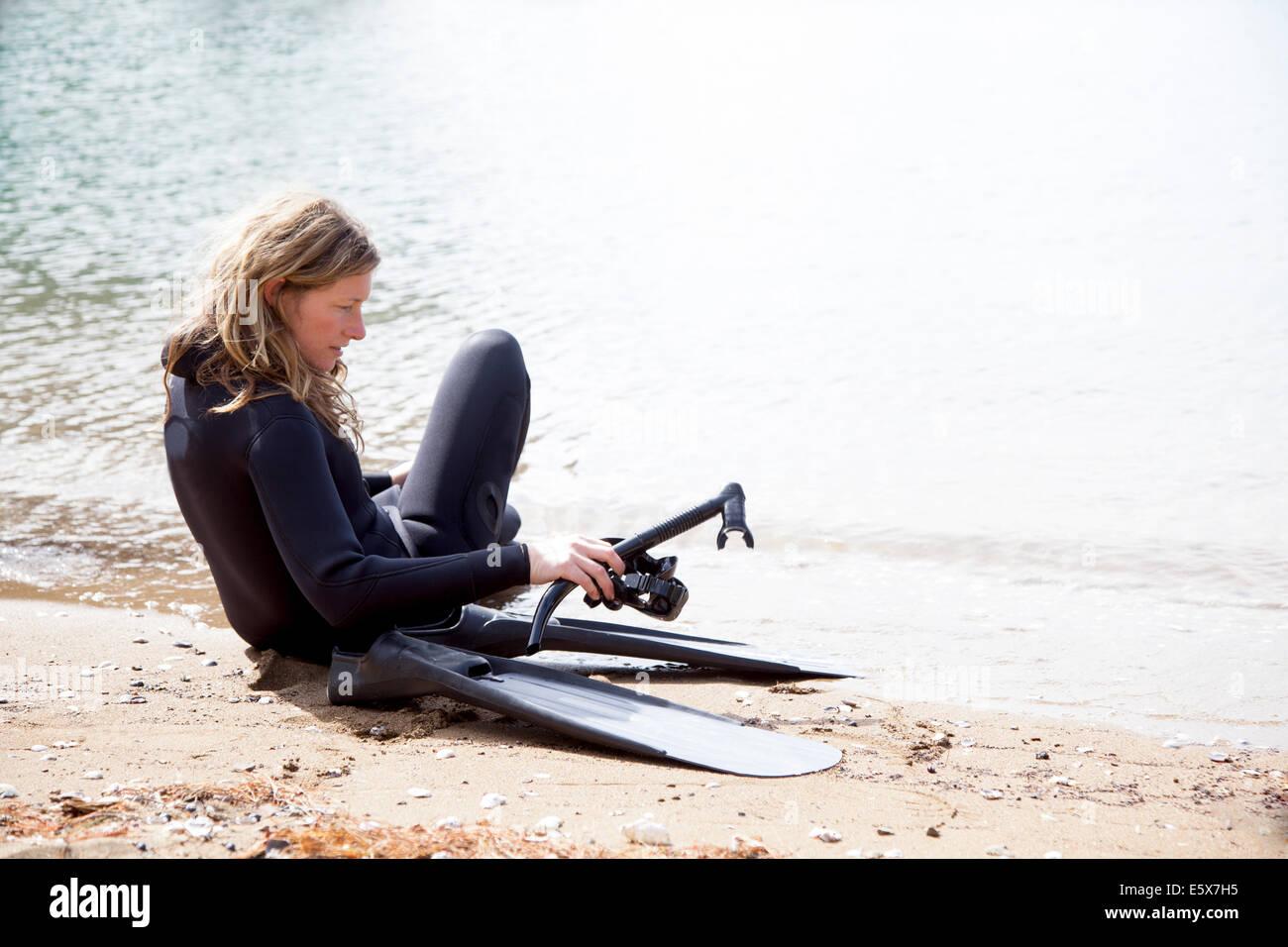 Mitte Erwachsenen weiblichen Taucher Tauchen am Strand wird vorbereitet Stockbild