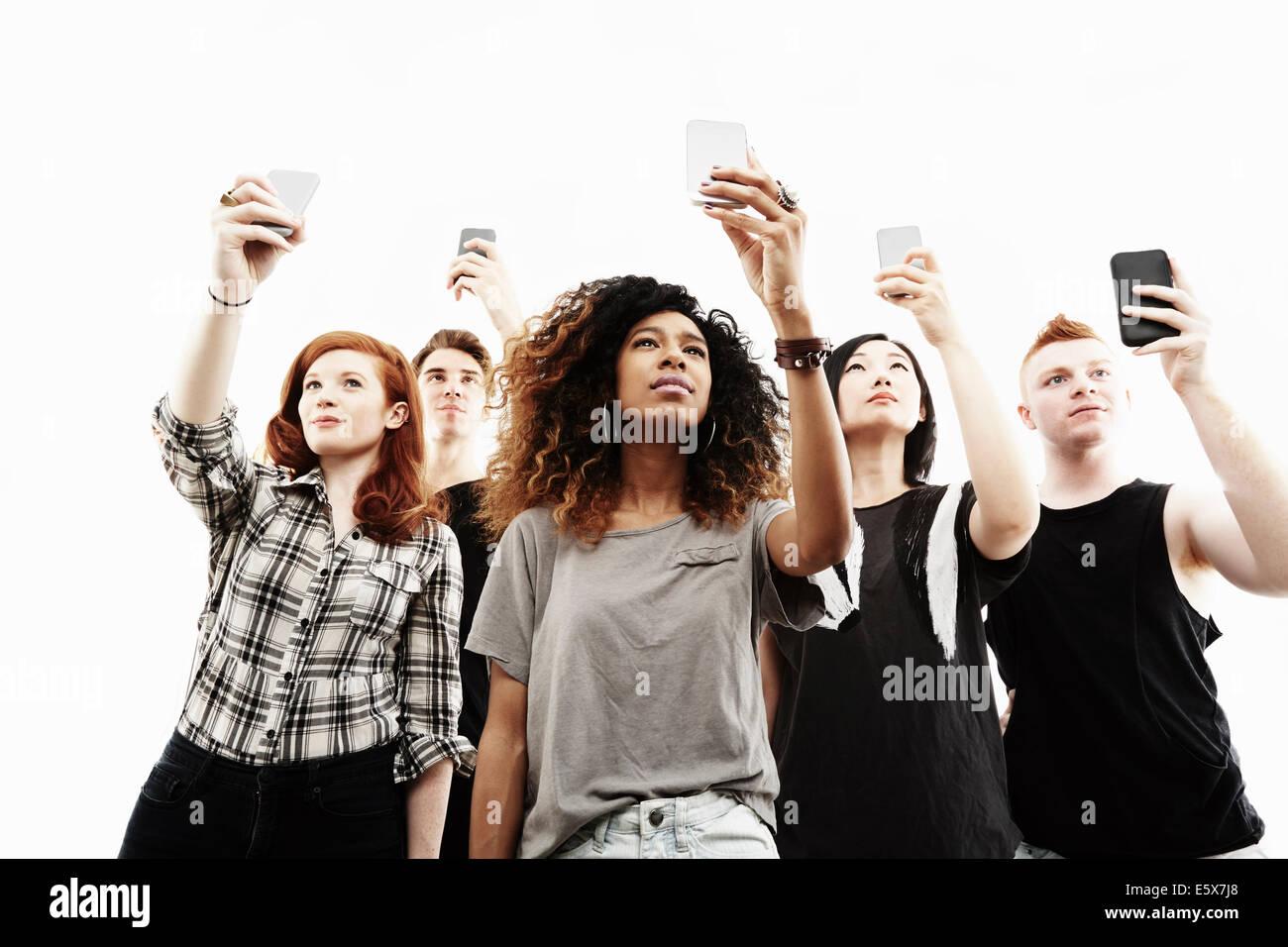 Studioportrait von fünf junge Erwachsene, die die Selfies auf smartphones Stockbild