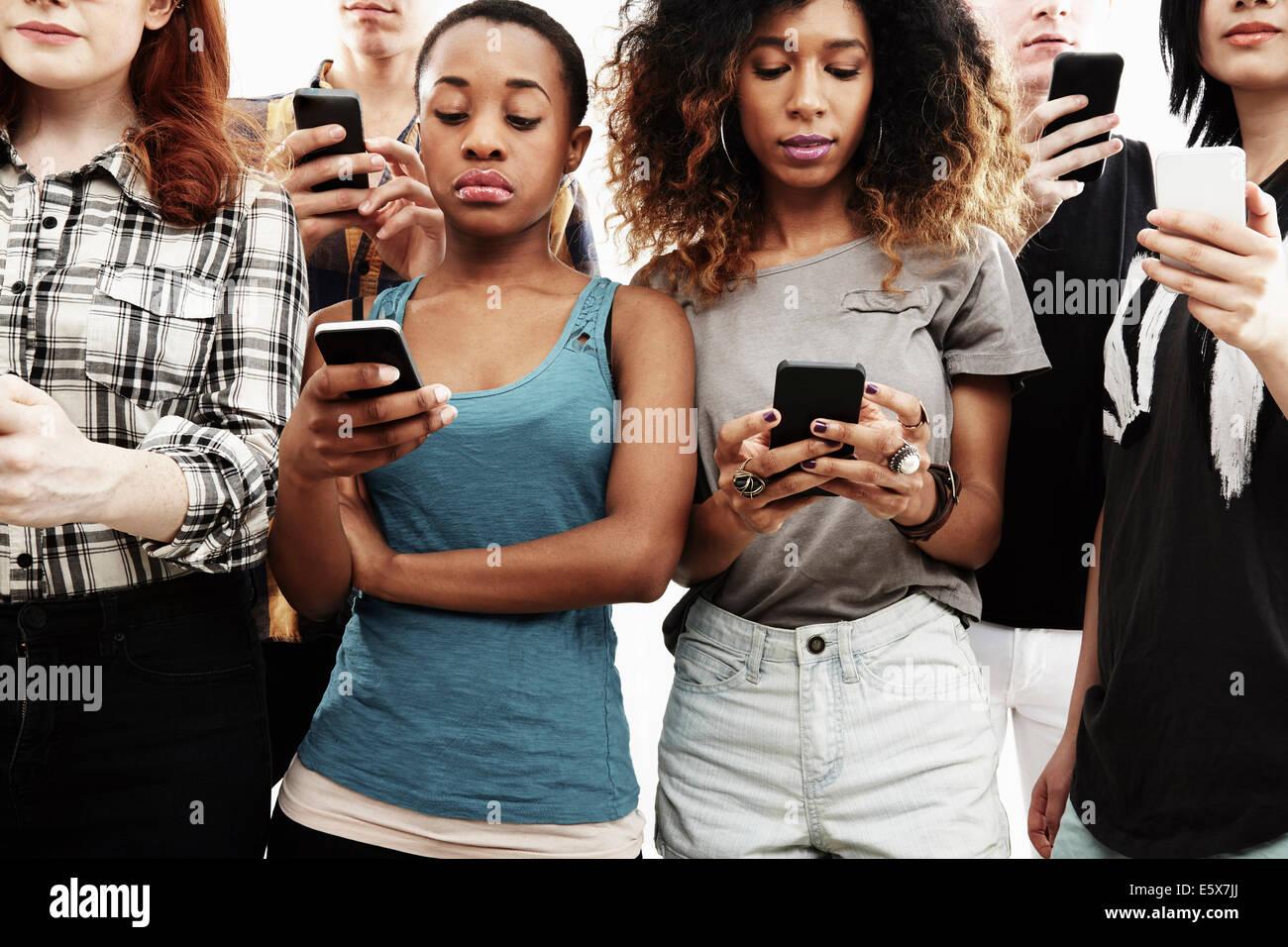 Studioaufnahme von sechs jungen Erwachsenen SMS auf smartphone Stockbild