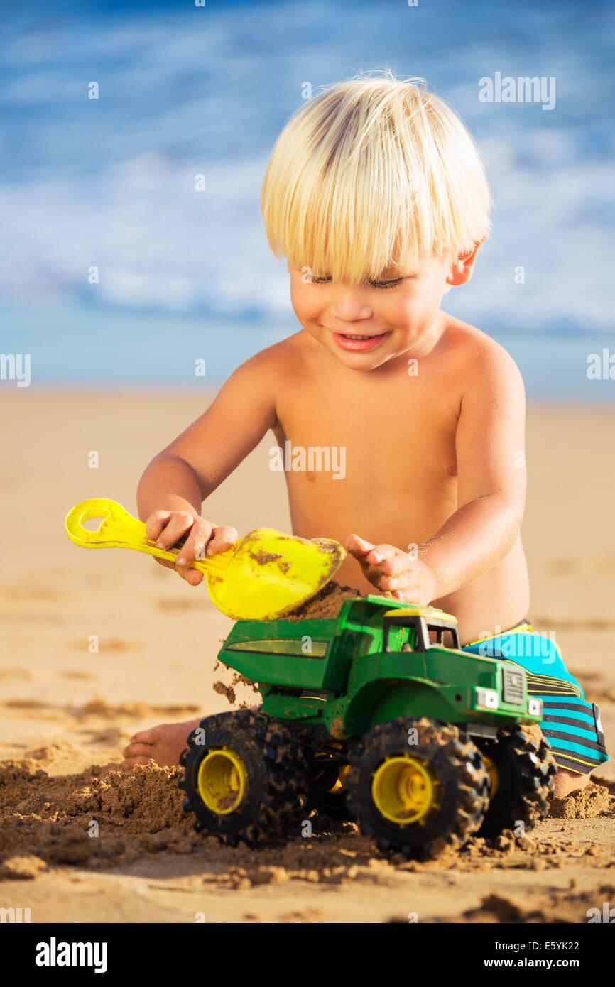 Glückliche junge spielt mit Spielzeug am Strand Stockbild