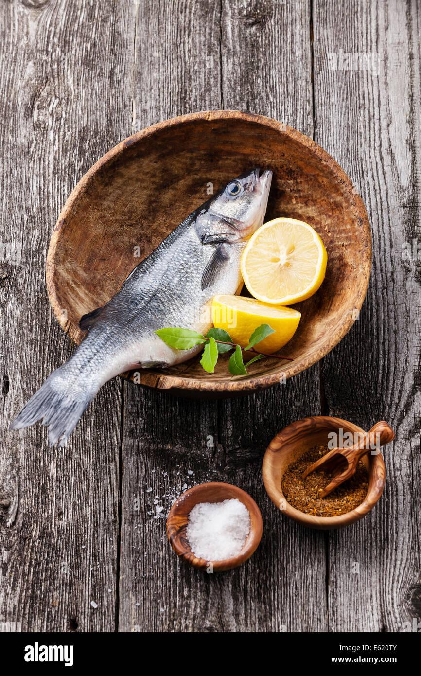 Seebarsch frischen rohen Fisch mit Salz, Gewürzen und Zitrone auf strukturierten hölzernen Hintergrund Stockbild