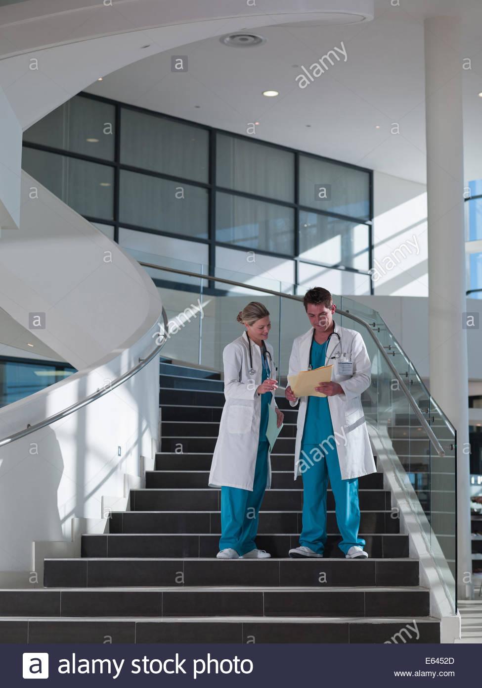 Ärzte zu Fuß hinunter Treppe im Krankenhaus Stockbild