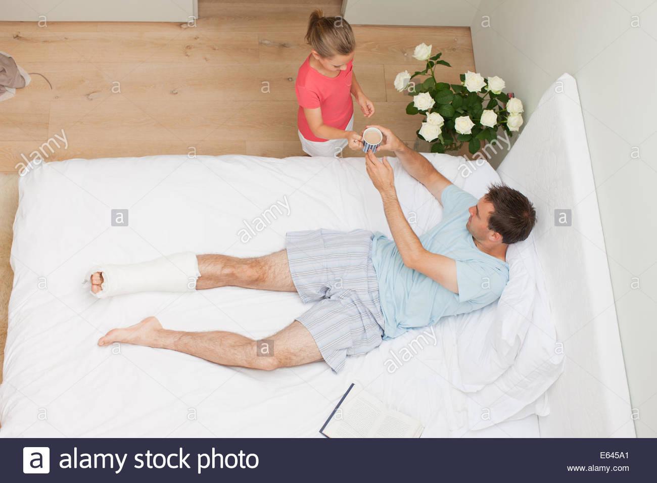 Tochter Vater mit gebrochenem Bein Kaffee bringen Stockbild
