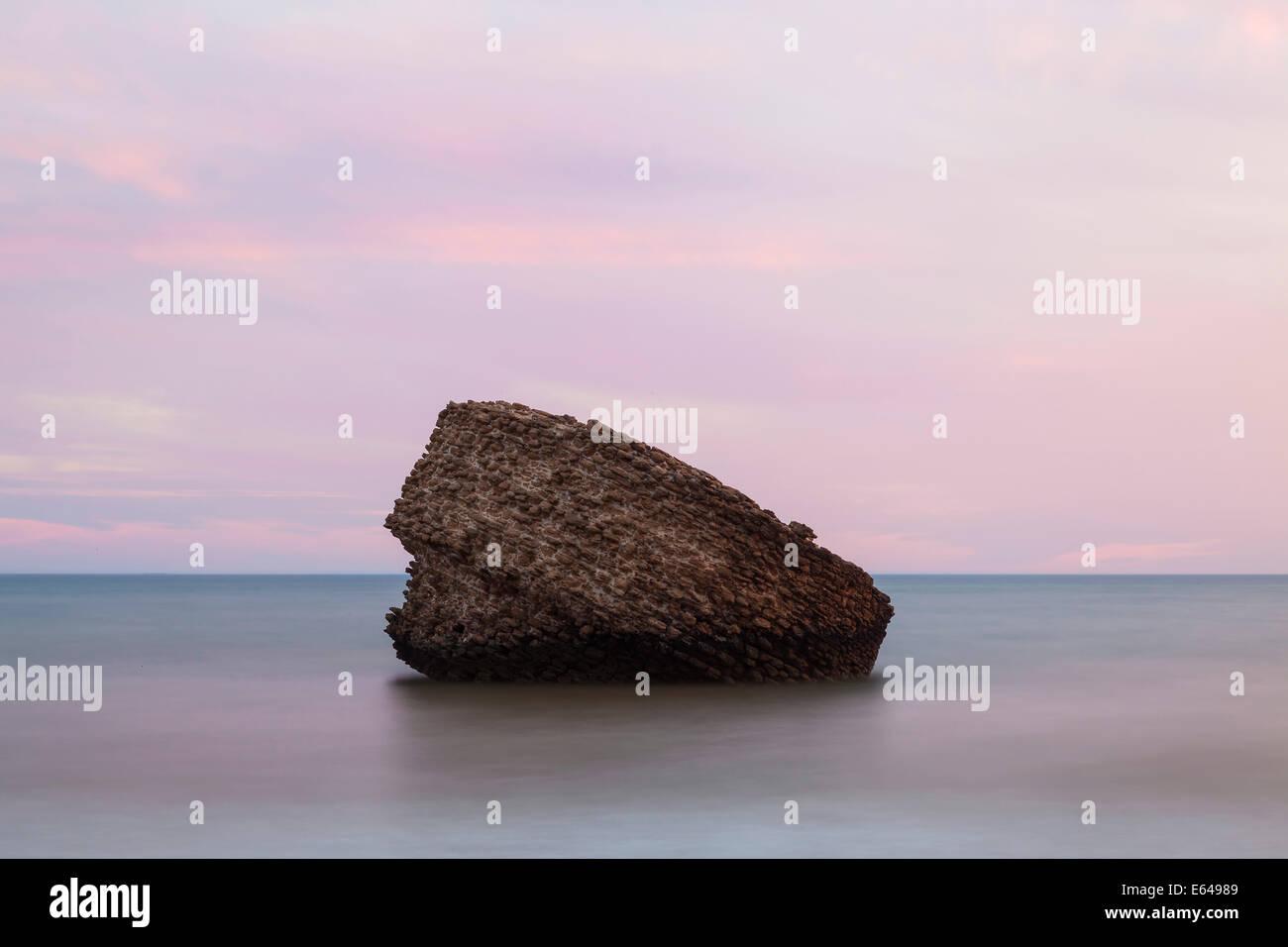 Rock (einem alten Wachturm oder Leuchtfeuer) am Strand von Matalascañas bei Sonnenuntergang, Andalusien, Spanien Stockbild