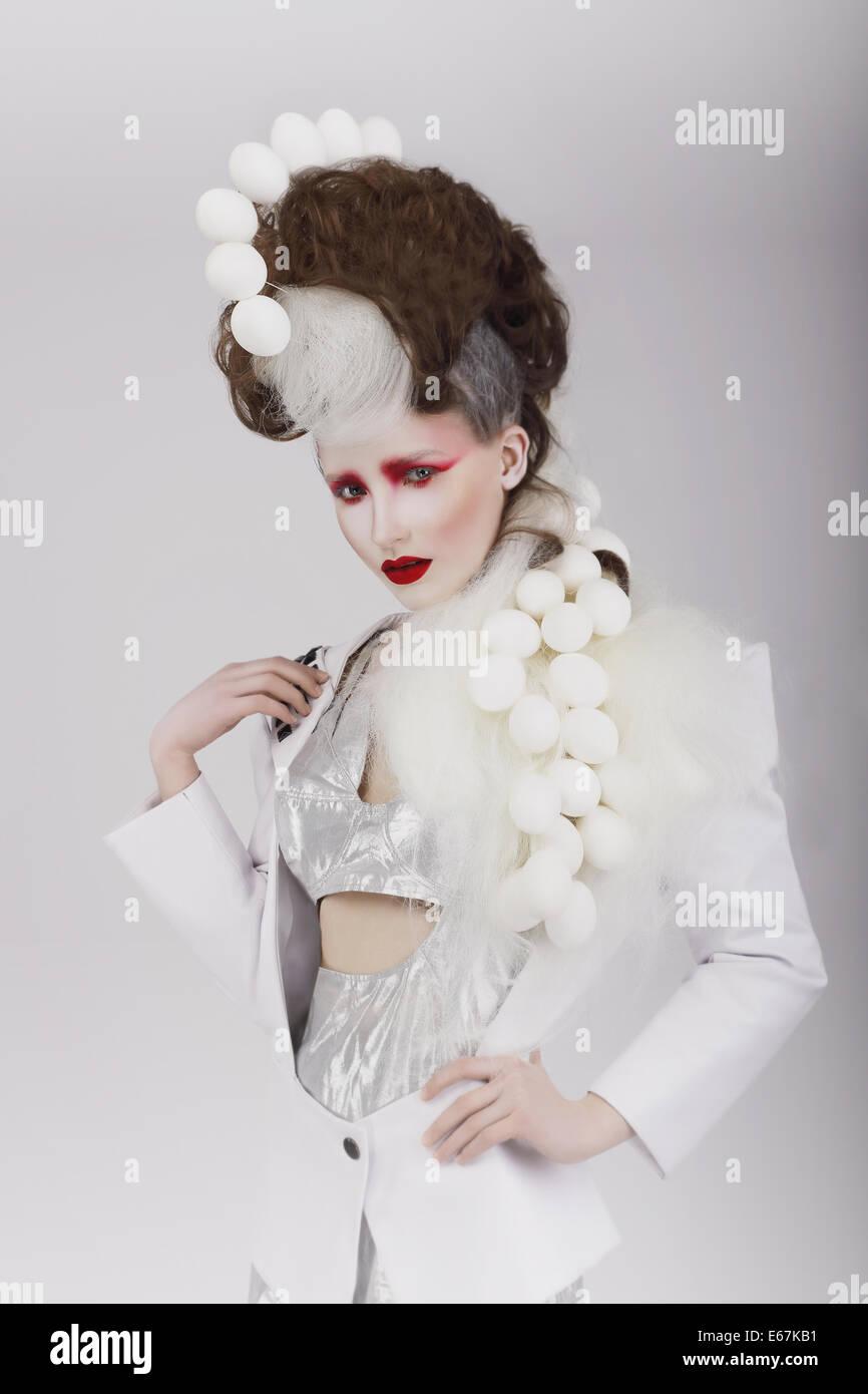 Haute Couture. Extravagante Frau in Cyber-Kostüm und theatralische Frisur Stockbild