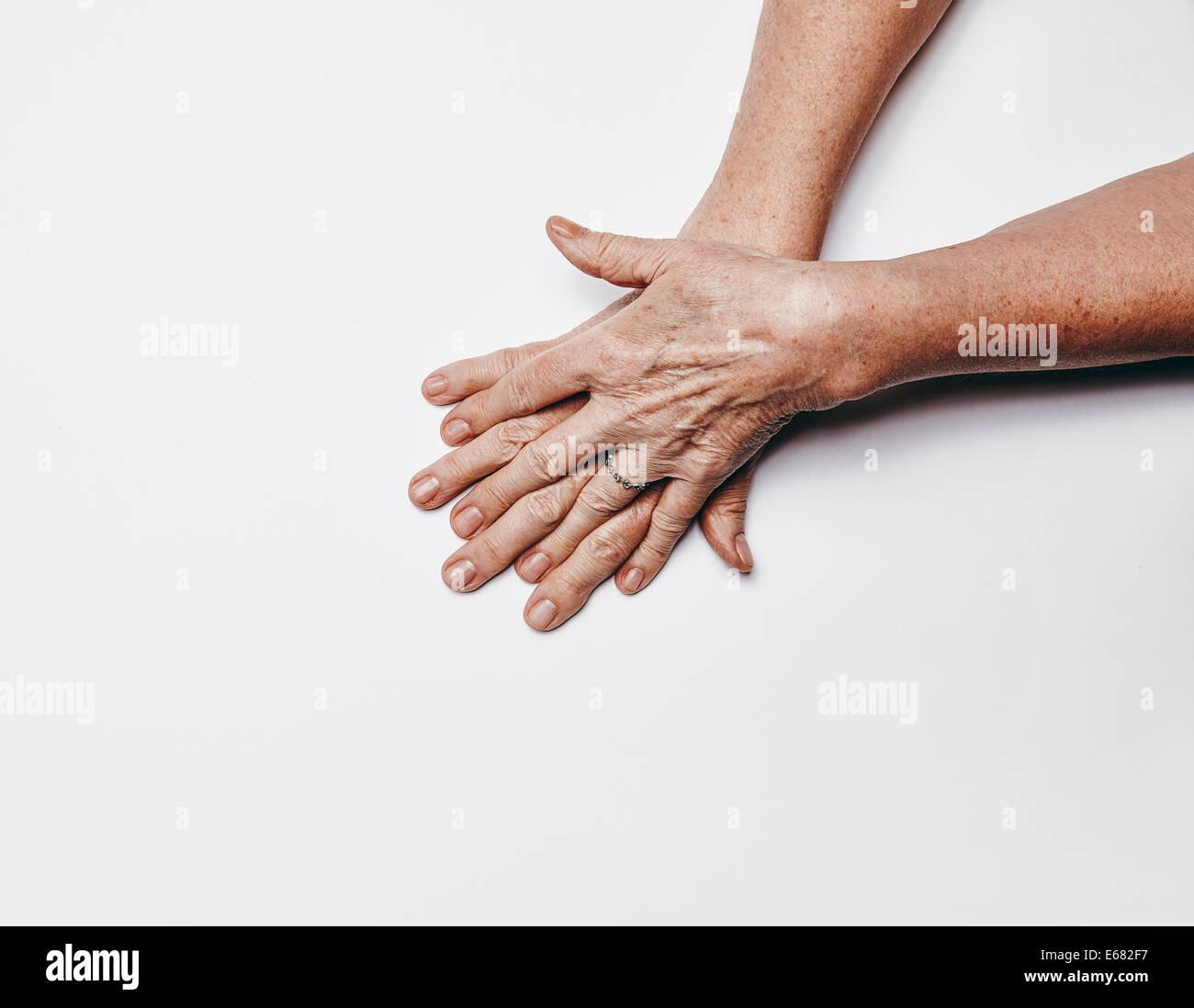Draufsicht der alte weibliche Hände mit Fingern überqueren. Ältere Frau Hände isoliert auf weißem Stockbild