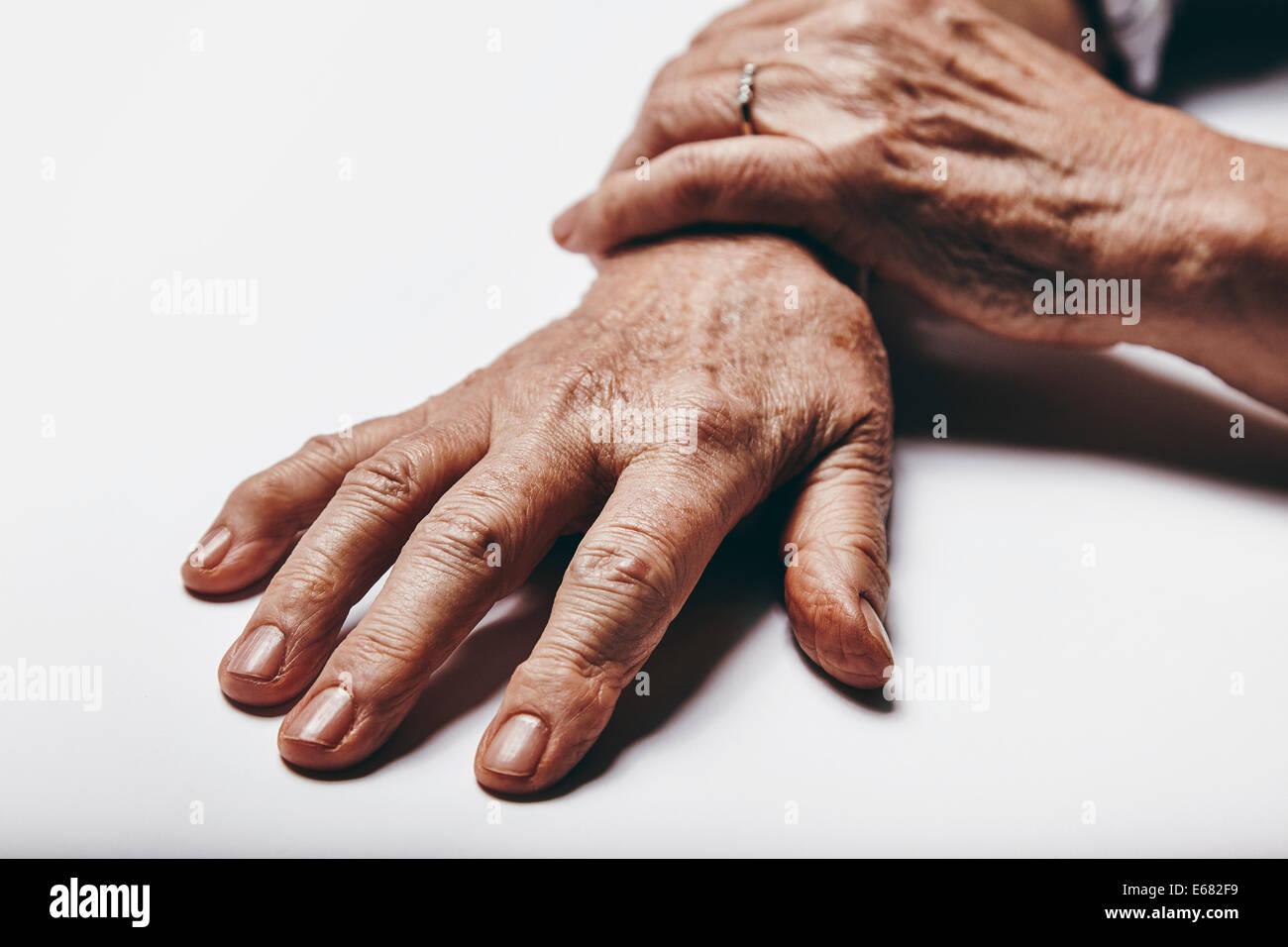 Makroaufnahme einer alten Frau die Hände auf eine graue Fläche. Finger der senior weiblich im Mittelpunkt. Stockbild