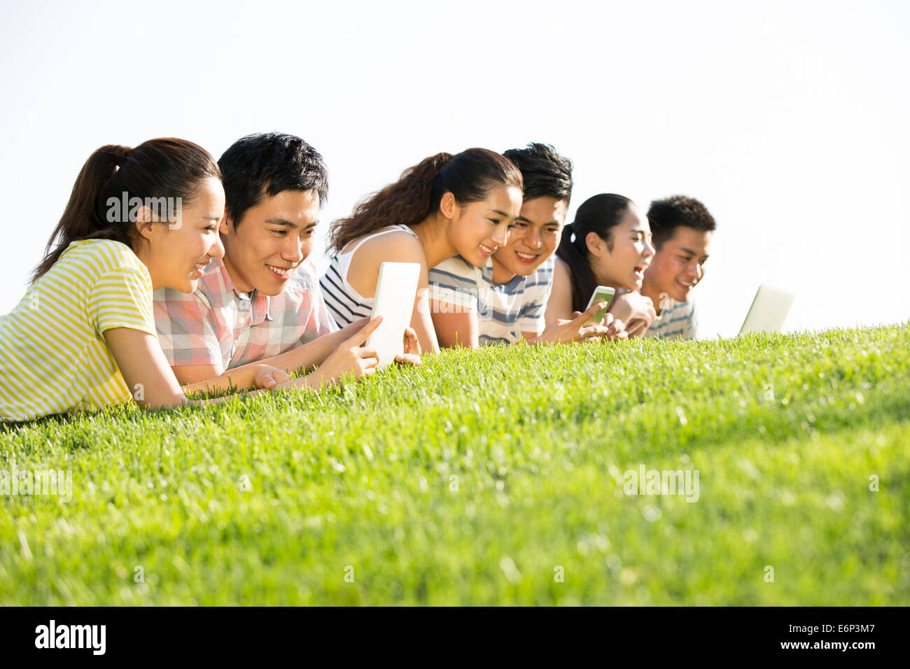 Fröhliche junge Erwachsene liegend auf Rasen spielen zusammen Stockbild
