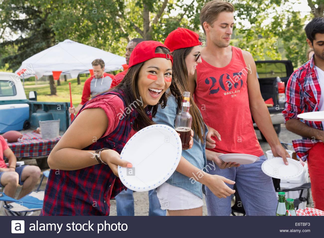 Frau, die Halteplatte an Heckklappe Grill im Feld Stockbild