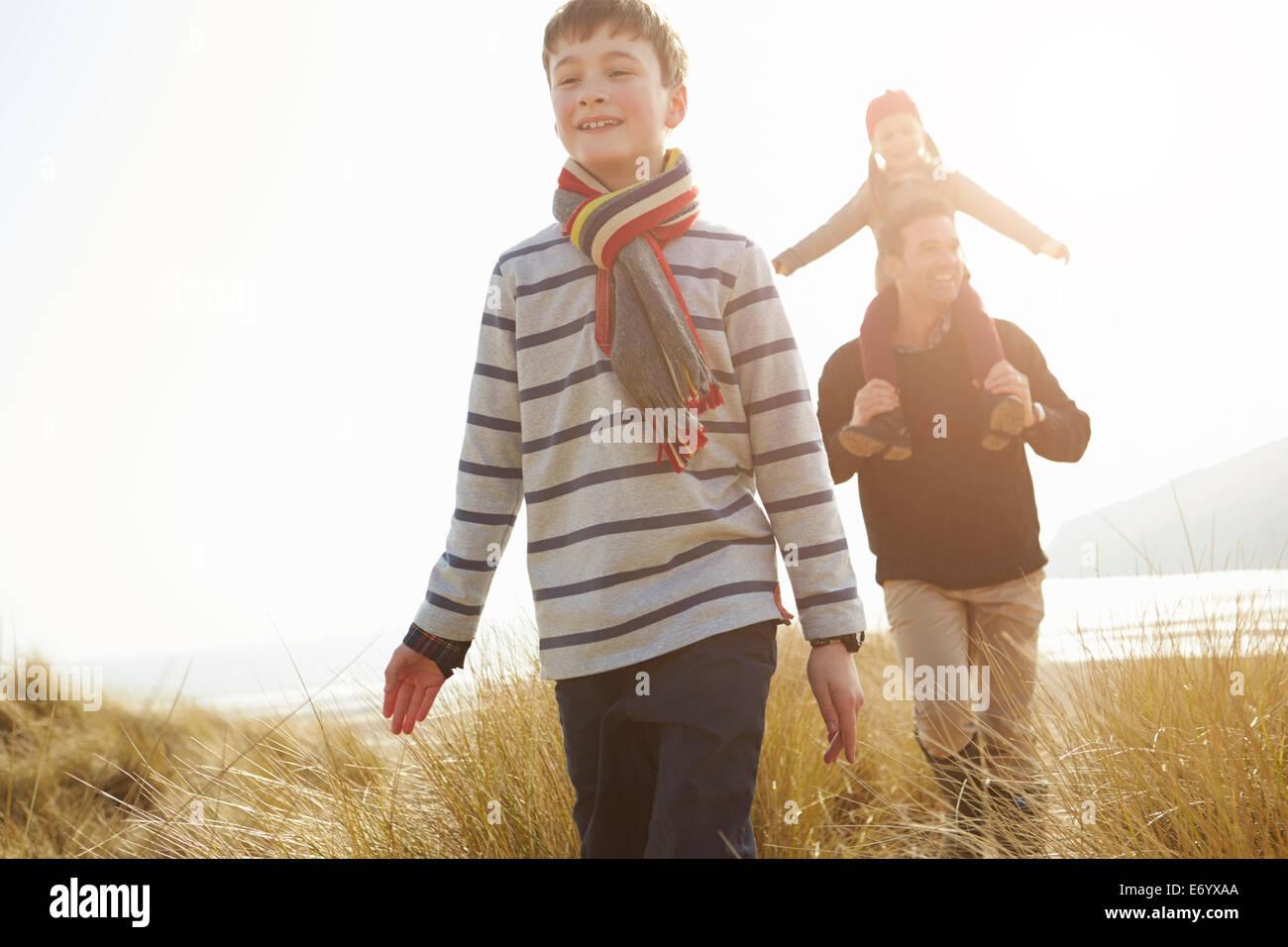 Vater und Kinder zu Fuß durch die Dünen am Strand von Winter Stockfoto